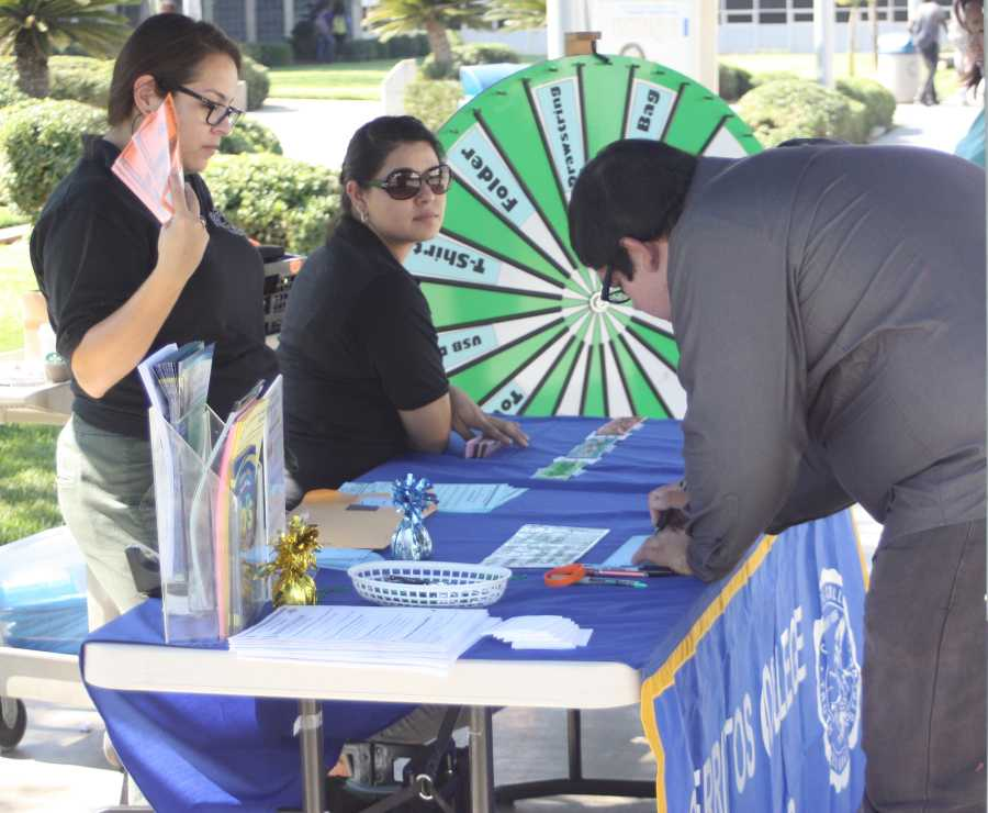 Rio Medina, outreach coordinator and student services assistant and Rosa Alejo, student services assistant helping students educate themselves about checks and financial aid. The booth was set up outside the library. Photo credit: Gustavo Lopez