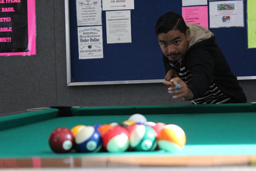 Gilbert Gonzalez, zoology major, starting up the game of pool by serving up and shooting off the first hit. He was playing pool with his other group of friends. He usually comes by Monday and Wednesday. Photo credit: Denny Cristales