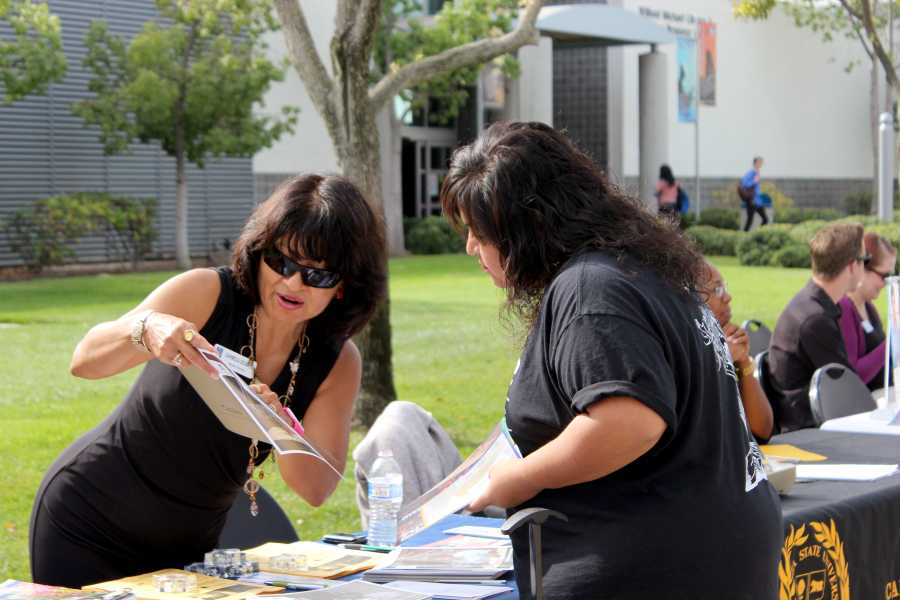 Cal State Fullerton's representative, Carmela Ocampo, gives a student information about her school. Students were able to get information about the school of their choice. Photo credit: Samantha Vasquez