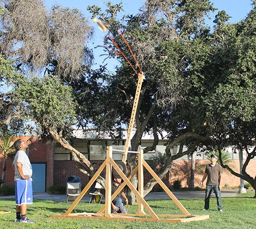Andres Moreno, computer science major, fires the ASET club's catapult. Assistant basketball Coach Jordan Littlejohn, left, watches with ASET secretary Sergio Serratos, right. Photo credit: Gustavo Lopez