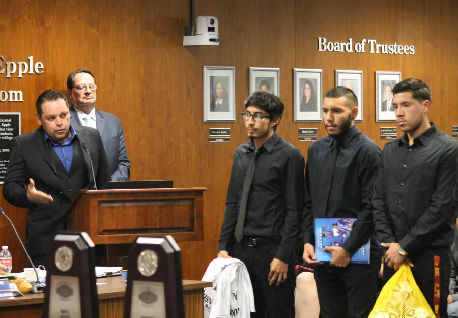 Men's soccer head coach Benny Artiaga (left) recognizing his roster and coaching staff on Jan. 21 at the Board of Trustees meeting.