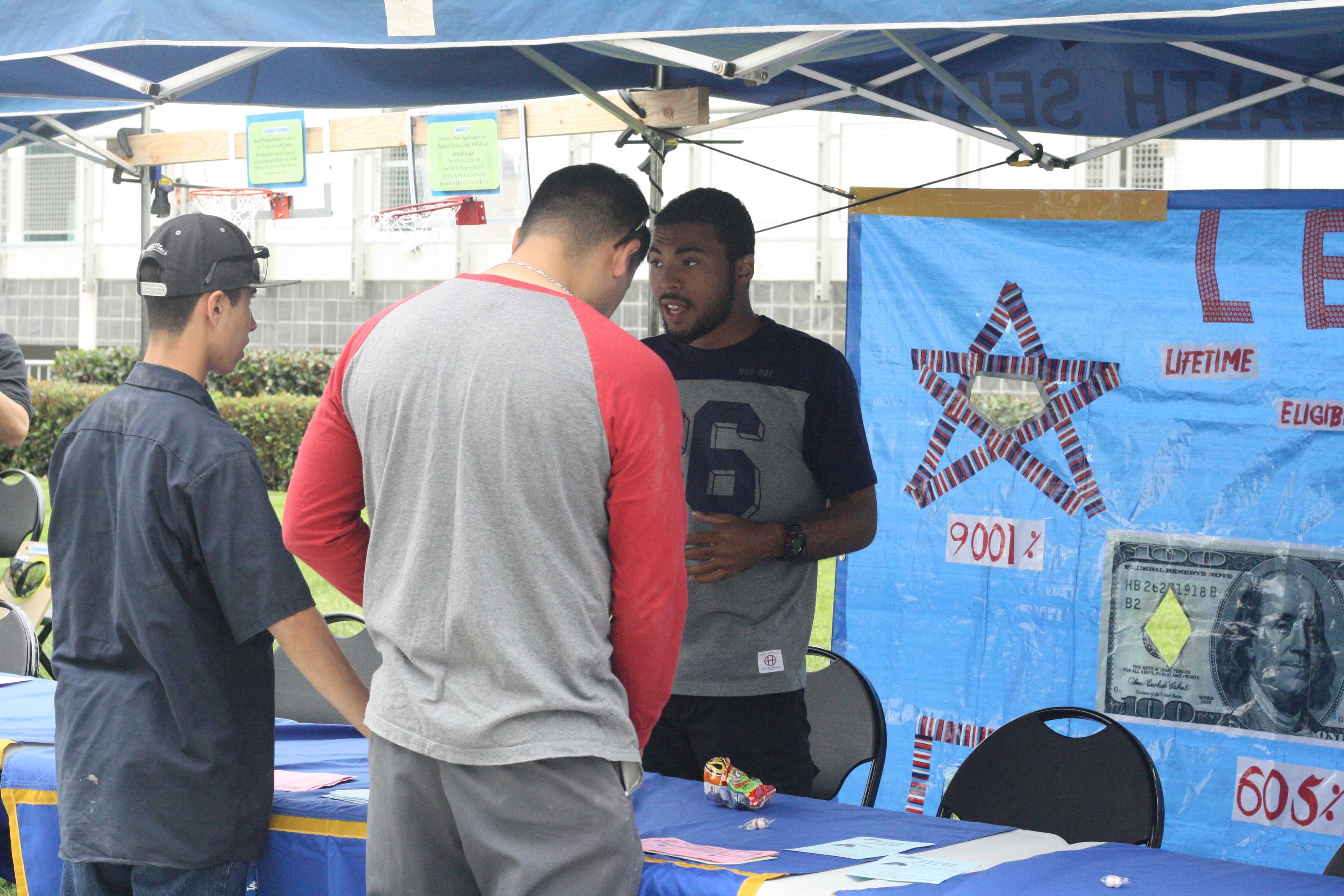 Computer Science major Cornelius Wells helps two students at a game booth during the Financial Aid Awareness Fair. The game booth provided information about FAFSA eligibility. Photo credit: Gustavo Lopez
