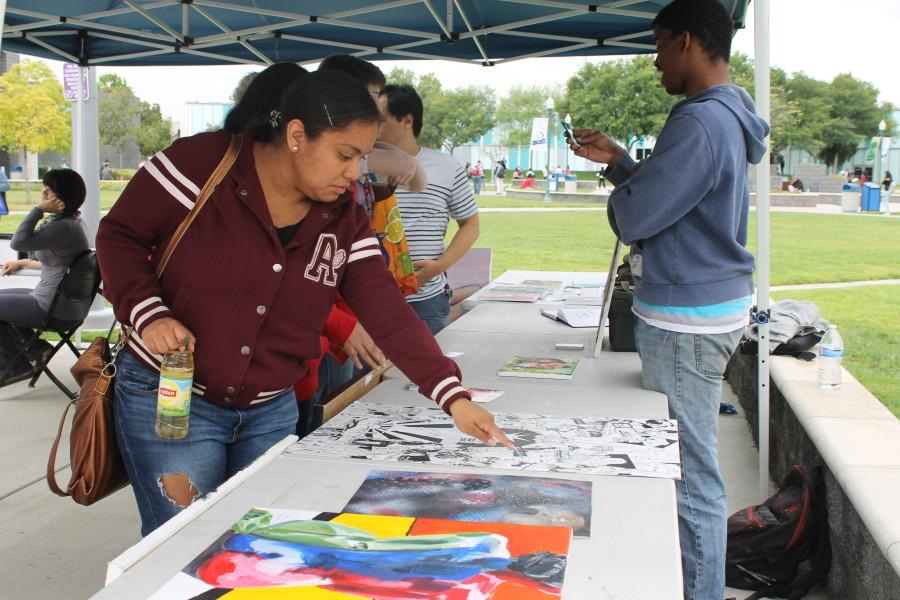 Students walked up to the art walk to check out the art done by both students and outside artists. Jasmin Galicia, left, was drawn in due to also being an art major. Photo credit: Lauren Torres