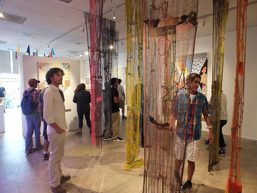 Students admire and walk through the art presented at the Cerritos College Art Gallery. The gallery featured abstract art from a variety of artist focusing on science, religion and other ideas.