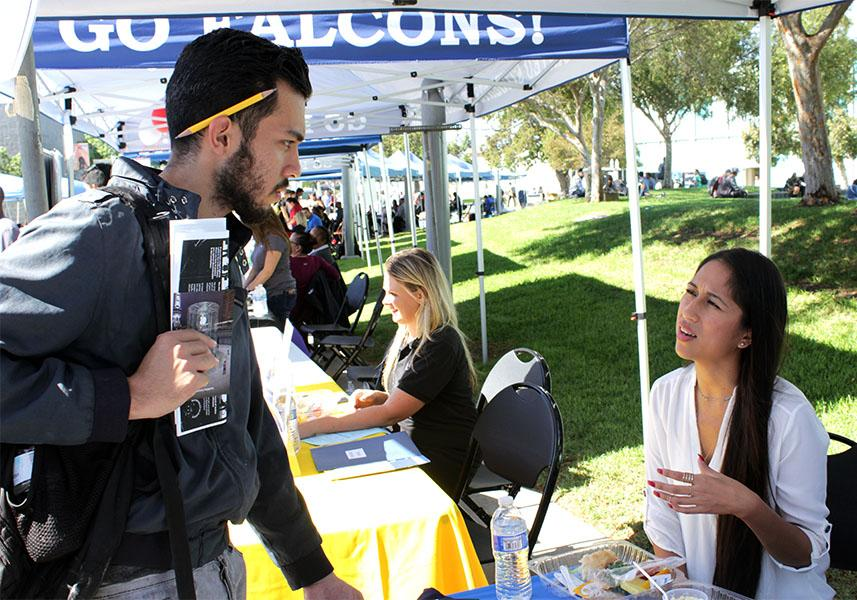 Administration of justice major, Michael Esqueda (left) listens to Ambria Aryes (right) about the open position at Davita. Esqueda is currently a part-time student who is browsing during the Job Fair on Wednesday. Photo credit: Bianca Salgado