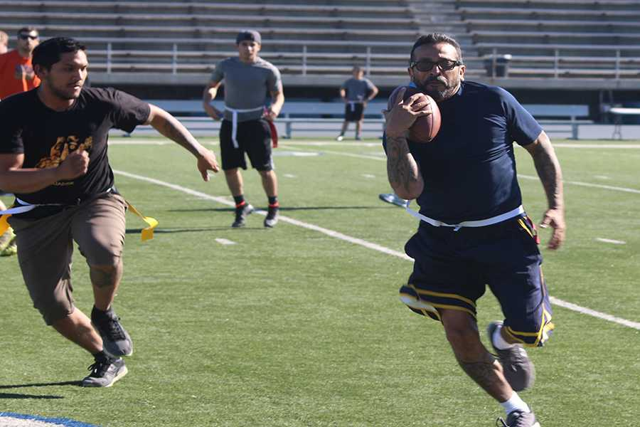 The first ever faculty and staff versus students flag football game was held at Falcon Stadium on Friday, Nov. 20. Politcal Science professor Dennis Falcon was on of the faculty members that participated in the event. Falcon(right) runs away from the the defending student(left) to try to get a first down for his team. Photo credit: Grester Celis-Acosta