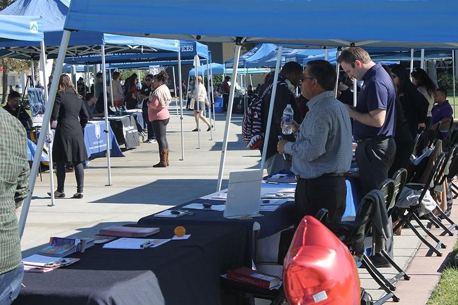 Students walk through the quad to learn about the universites and what the schools are offering. University representatives prepare to give Cerritos College students the information they need. Photo credit: Ethan Ortiz