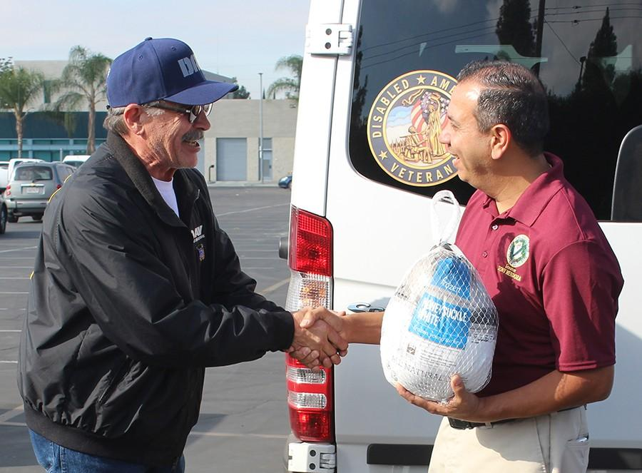 State senator Tony Mendoza greets a community member at Operation Gobble. This is Mendoza's first year participating in the event as a senator. Photo credit: Gustavo Lopez