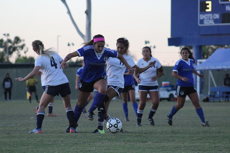 Freshman Natlie deLeon dribbles through two of El Camino's defenders. She leads the team with fifteen assists in the season. Photo credit: Christian Gonzales