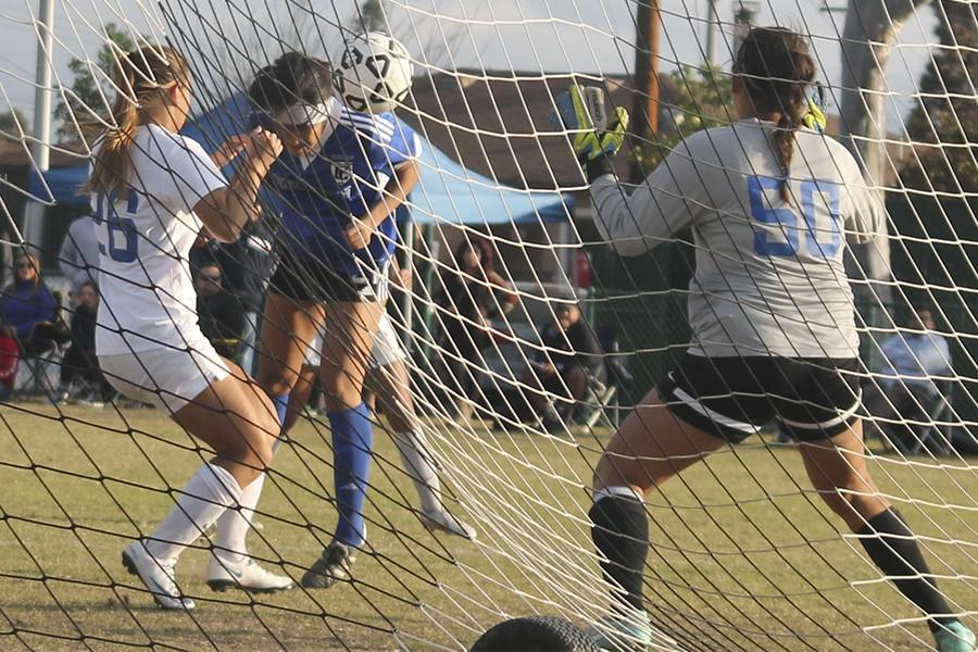 Amber Whitmore, Forward No. 21, (blue jersey) puts a header away past San Bernardino Valley College's defender and goal keep. The goal was the second of the match. Photo credit: Amanda Del Cid