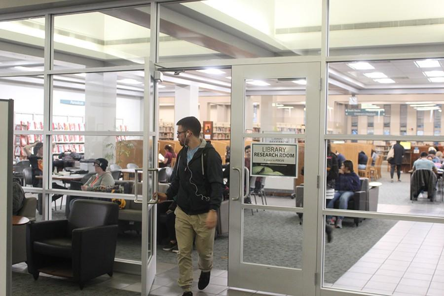 Zach Sipe, philosphy major, exiting the now closed off main stacks in the library. The divider had been planned for years by Carl Bangston but it wasn't until a recent increase in noise complaints that the divider was added. Photo credit: Gustavo Lopez
