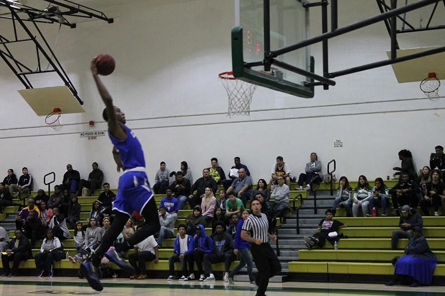 Jamal Watson takes flight for a one-handed slam. Watson finished with 11 points, eight rebounds, and two blocks. Photo credit: Taylor Ogata