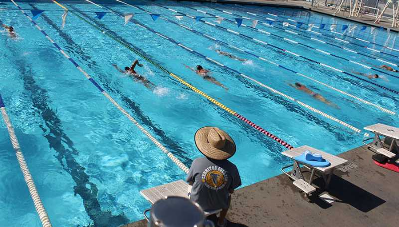 Men's swimming coach, Joe Abing, watches over the swim team as they are warming up. Abing prepares the team for the upcoming swim meet on Friday. Photo credit: Terrel Emerson