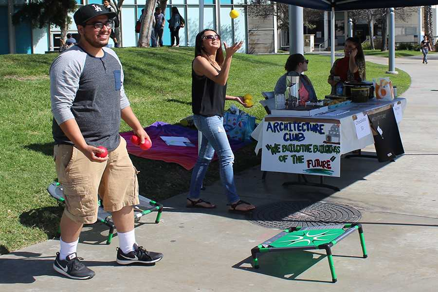 Architecture and technology club members, Jesse Magellan (left) and Krisandra Perez (right), set up a game for their fundraiser. Funds raised from the fundraiser will go towards an event for the students. Photo credit: Briana Hicks