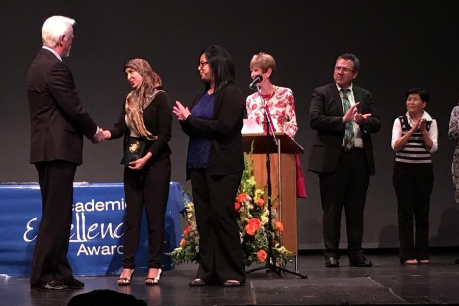 Microbilogy major Zeinab Chahine receives award from Trustee Bob Arthur at the Academic Excellence Awards on Thursday, March 31. She was escorted by professor Santos Rojas. Photo credit: Karla Enriquez