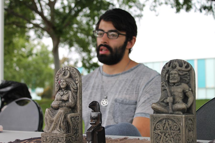 Michael David, part of the Wiccan Club sits at a club table in Falcon Square with artifacts. David created the club in hopes of spreading diversity and finding other people who practice the religion. Photo credit: Gustavo Lopez