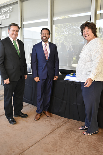 Patrick O'Donnell Director of Information and Technology (left), Cerritos College President  Dr. Jose Fierro (center) and Sue Parsons Director of Educational Partnerships and Programs (right) posing in front of the cake for the Outstanding Manager of the year award celebration. For both O'Donnell and Parsons it was their first time getting the award and they shared the moment with their mothers, other family and friends. Photo credit: Perla Lara