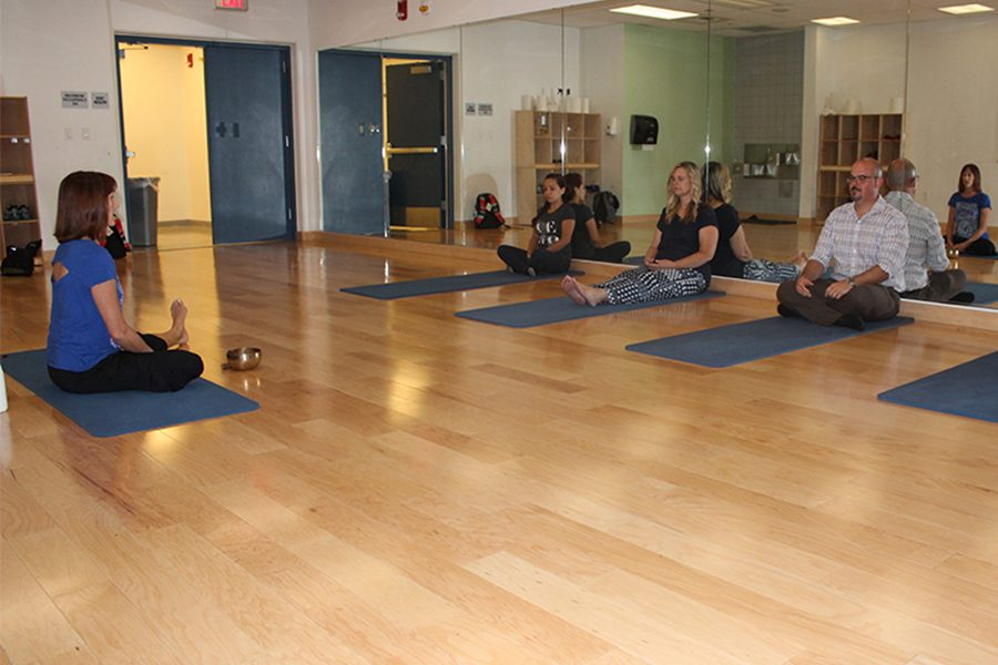 Meditation time with instructor Laurie Angress, she's sitting down on the center of the class facing towards the students and staffs. On the left side we have a student, followed by Janice O' neal, and Steven Lavigne, staff members from DSPS Building. Photo credit: Lizette Sainz