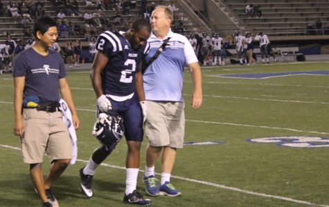 Linebacker Kijon Washington is being assisted off the field by Brian Cable and an assistant after suffering an ankle injury in Saturday nights game. He would later return to the game after recieving treament from the athleteic training staff.