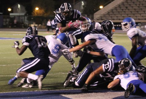 Running back Kishawn Holmes hurdles over defenders en route to the end zone. Holmes scored three rushing touchdowns on the night after not scoring a rushing touchdown all season long.
