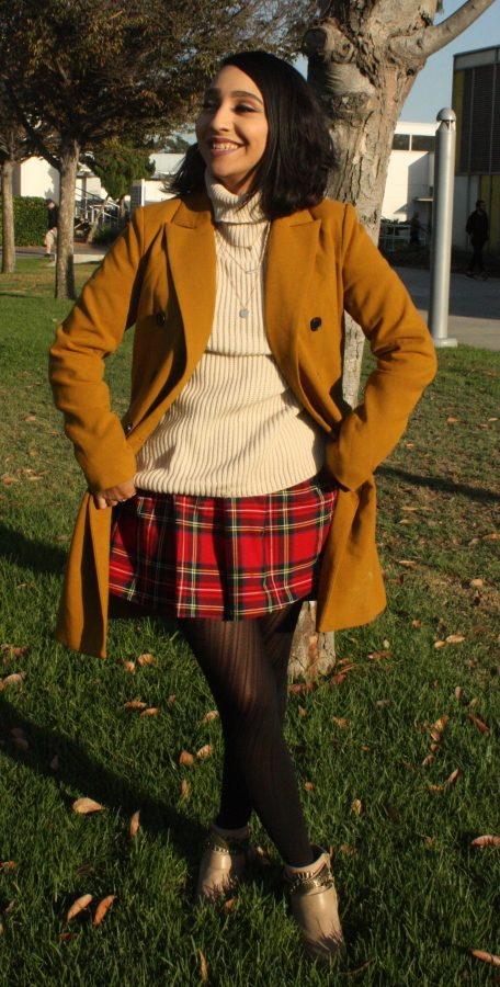 Managing Editor Karla Enriquez demonstrates a fall outfit. Coats and plaid are a major hit for fall fashion. Photo credit: Briana Velarde