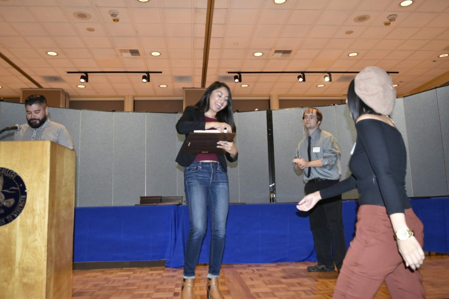 Managing editor Karla Enriquez walks unto the stage to pick up her journalism award. Enriquez won second place for the mail-in news photo contest. Photo credit: Perla Lara