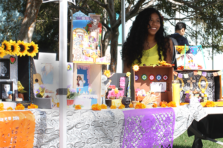 Psychology major and MEChA member Stephanie  Nunez stands behind an altar for DÍa de los Muertes to memorialize loved ones who have passed. The club also had traditional snacks and face painting available for students to try. Photo credit: Bianca Martinez