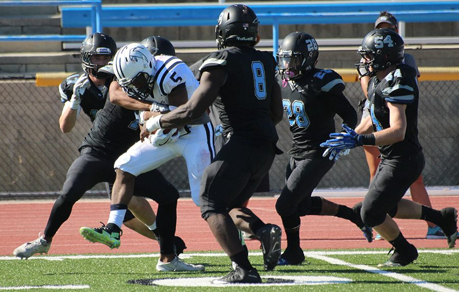 Cerritos+running+back+Kishawn+Holmes+is+gang+tackled+by+5+Moorpark+Raiders.+Although+he+rushed+30+times+for+185+yards%2C+the+team+was+not+able+to+successfully+earn+a+win+over+the+Raiders%2C+falling+35-28.