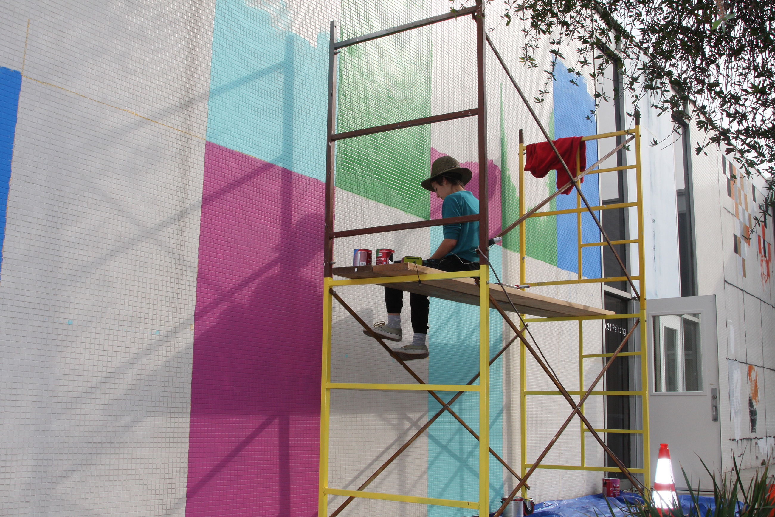 Yomina Del Castillo painting the old Fine Ats building. The community will be able to paint over the colorful paint at the FAR-Bazaar event. Photo credit: David Jenkins