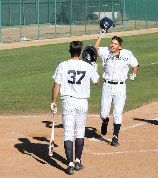 Freshman shortstop Ramon Bramasco high fives teammate Derrick Edwards after his fourth inning homerun against Santa Barbara. Bramasco finished with a game high three RBI's in the teams win.