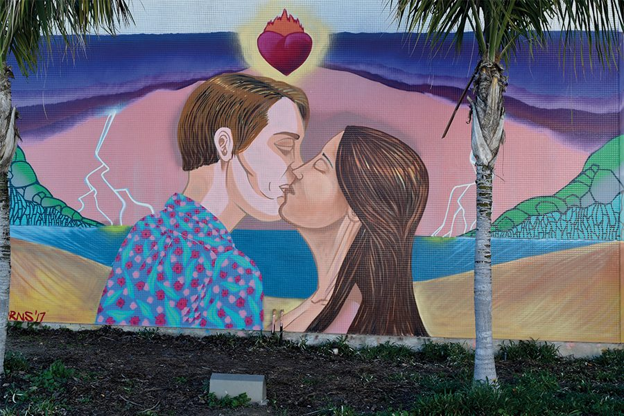 "Artist Tommy Burns Mural, ""Bolt from the blue: Kiss of the tides"" on the wall of the old Fine Arts Building at Cerritos College, done over the span of one week for the F.A.R. Bazaar event. Burns chose to paint what he calls a ""simple romantic"" art that everyone who saw could understand and relate to. Photo credit: Perla Lara"