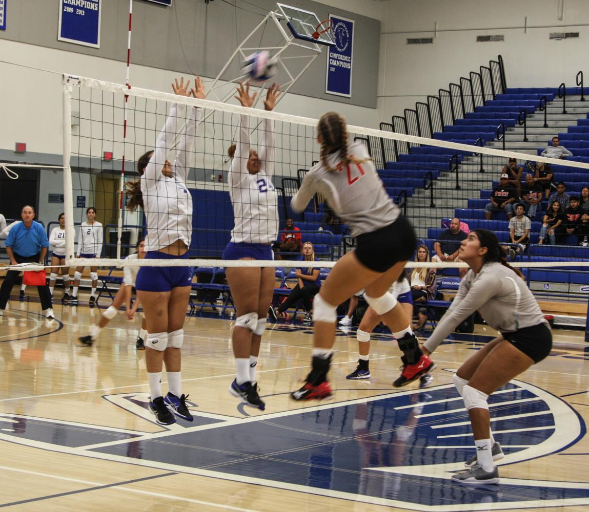Falcon's (white and blue) Natalty Reynoso, 4 and Cecila Burroughs, 24 defended a spike by Santa Ana's (red and black) Mikelle Taylor, 21.  Although the Falcons made a comeback within the third and fourth set, Santa Ana was able to gain the upper hand and defeat the Falcons 3-2. Photo credit: David Jenkins