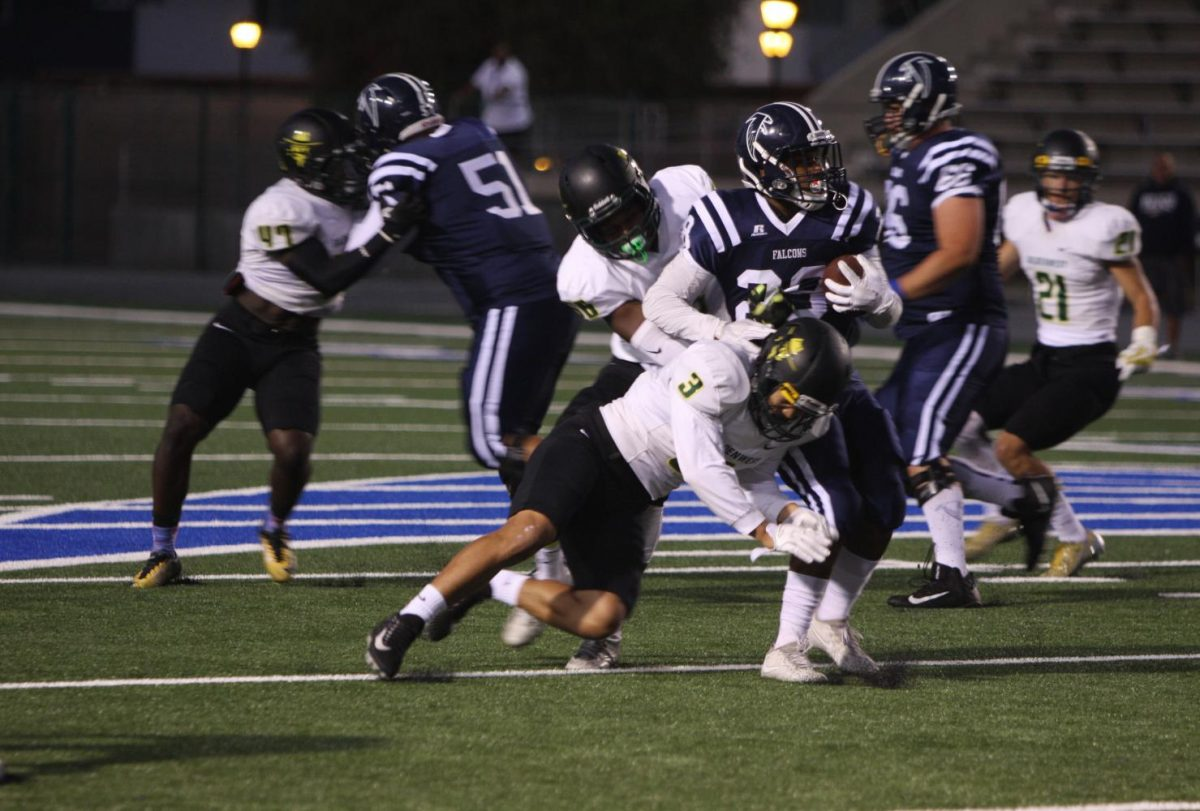 No. 28 running-back for the Falcons, Querale Hall driving the ball down the field while dodging tackles. Hall was able to get a touchdown for the Falcons on Sept. 23 against Golden West. The Falcons defeated Golden West 36-23. Photo credit: David Jenkins