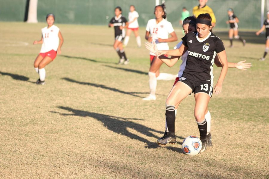 No. 13 Stephanie Nava, freshman--midfielder, guides the ball as she is hounded by a defender. Falcons won game against Chaffey College 2-1, in a Nov. 21 playoff game. Photo credit: Jah-Tosh Baruti