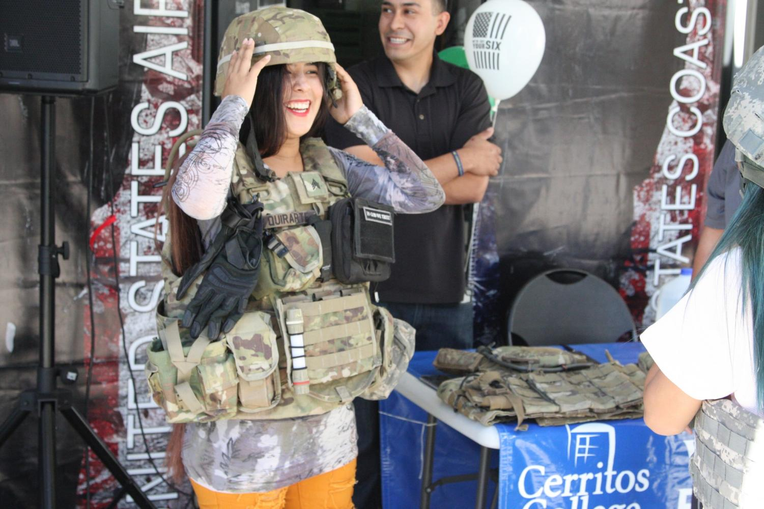 Kemberly Enriquez trying on army gear with the permission of the veterans. Enriquez and the Homecoming Queen Jazmine Jose were taking pictures wearing the gear. Photo credit: David Jenkins