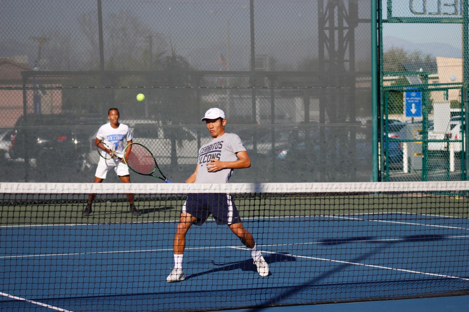 Freshman, Kent Hunter and Sophomore Kwangeun Lee during their doubles match. Lee raises his racket for a quick save.