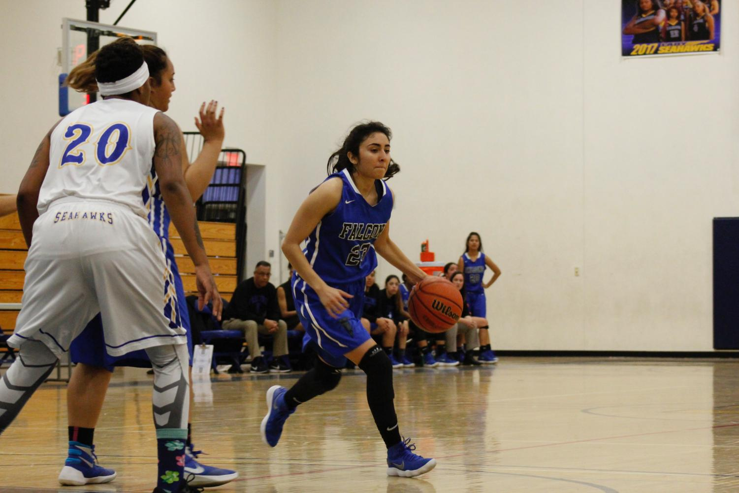 Freshman, Guard No. 23 Jessica Gomez dribbles the ball past the defender. Gomez aimed to try and open up the defense to get a open shot.