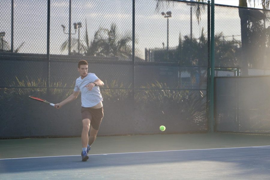 Alex+Prokopchuk+has+steady+eyes+on+the+tennis+ball%2C+while+his+hands+are+in+full+motion+to+swing.+Cerritos+College+won+the+matches+overall+9-0.+