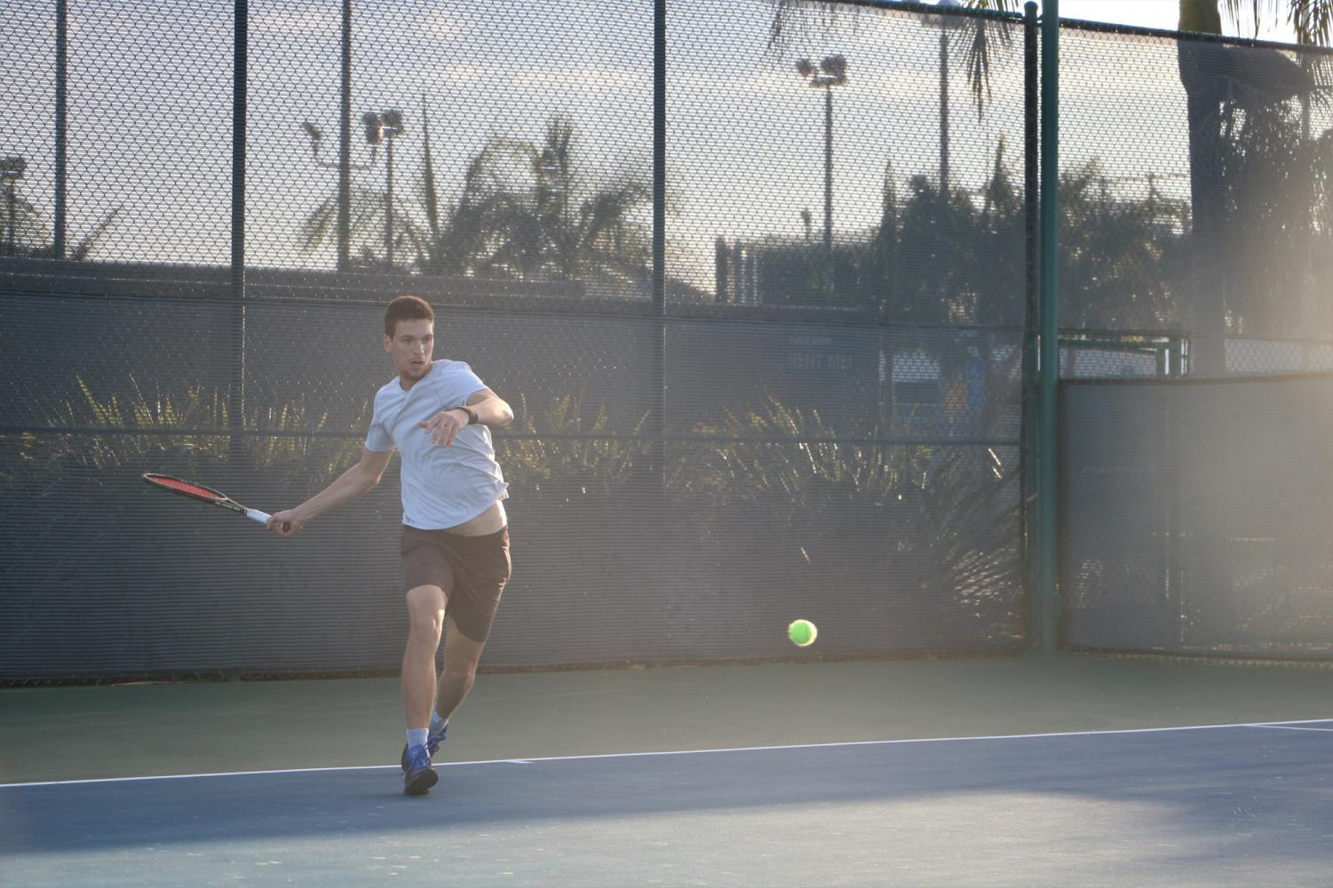 Alex Prokopchuk has steady eyes on the tennis ball, while his hands are in full motion to swing. Cerritos College won the matches overall 9-0.