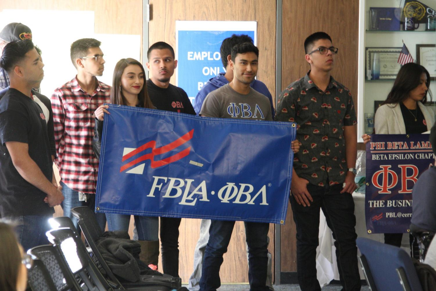 Phi Beta Lambda display their club banners during their presentation to the Associates Students of Cerritos College. They end the presentation by screaming,