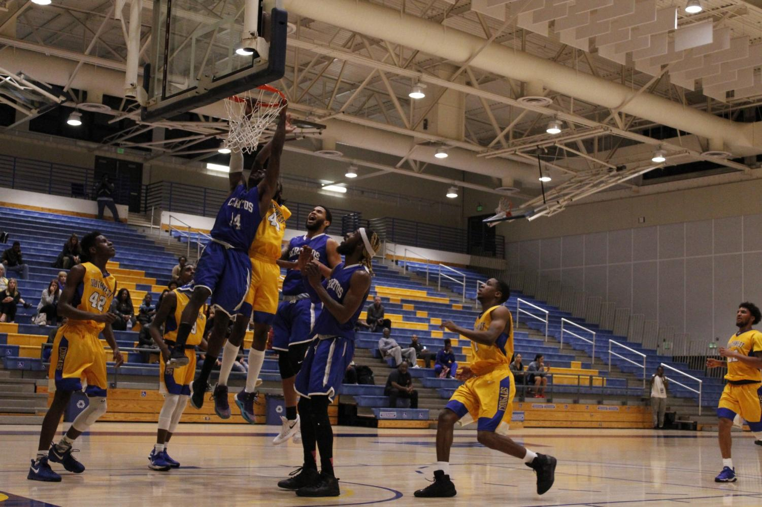 No. 14 Keshaun Mack leaps for a powerful dunk attempt. Mack finished the game with 14 points and four made threes.