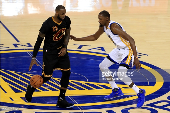 Cleveland Cavaliers forward LeBron James dribbles the ball up against Golden State Warriors forward Kevin Durant in the 2017 NBA Finals. Warriors won the Finals in five games over the Cavs. Photo credit: Getty Images