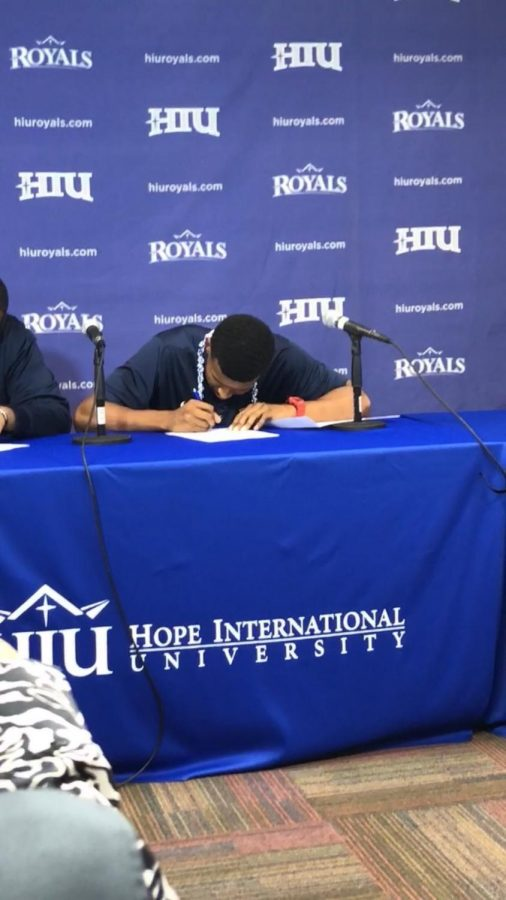 Forward Jonathan Guzman signing a national letter of intent to Hope International University. He will be receiving a two-year scholarship to attend the program. Photo credit: Malik Smith