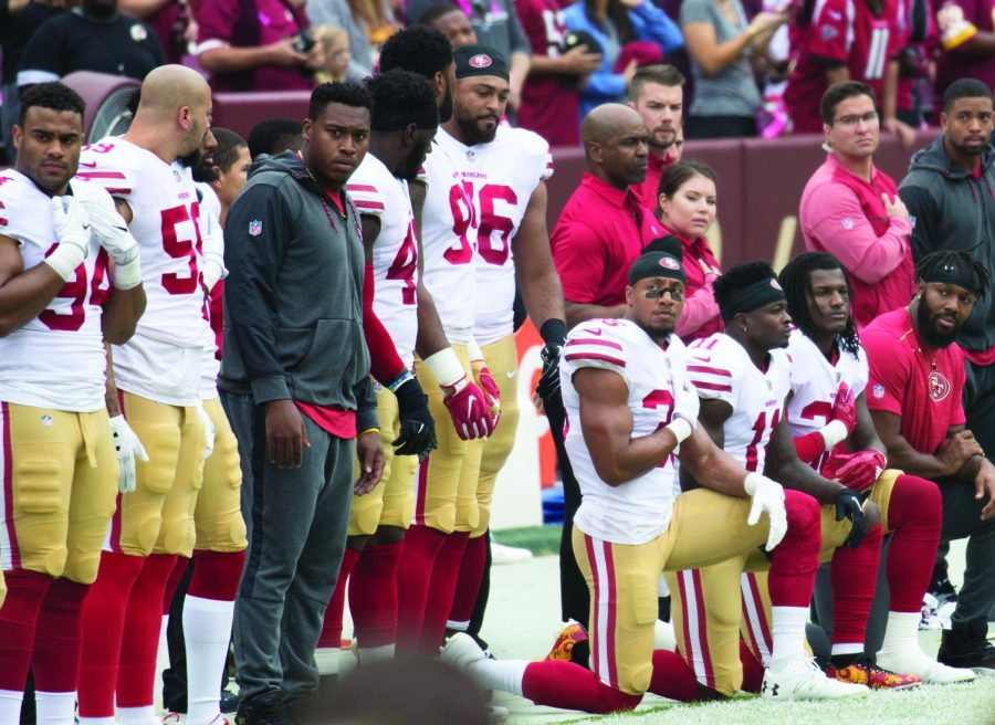 Some members of the San Francisco 49ers kneel during the National Anthem before a game against the Washington Redskins at FedEx Field on October 15, 2017 in Landover, Maryland. Photo credit: Keith Allison Creative Commons