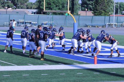 The Cerritos College football team practicing plays before the start of the actual scrimmage.