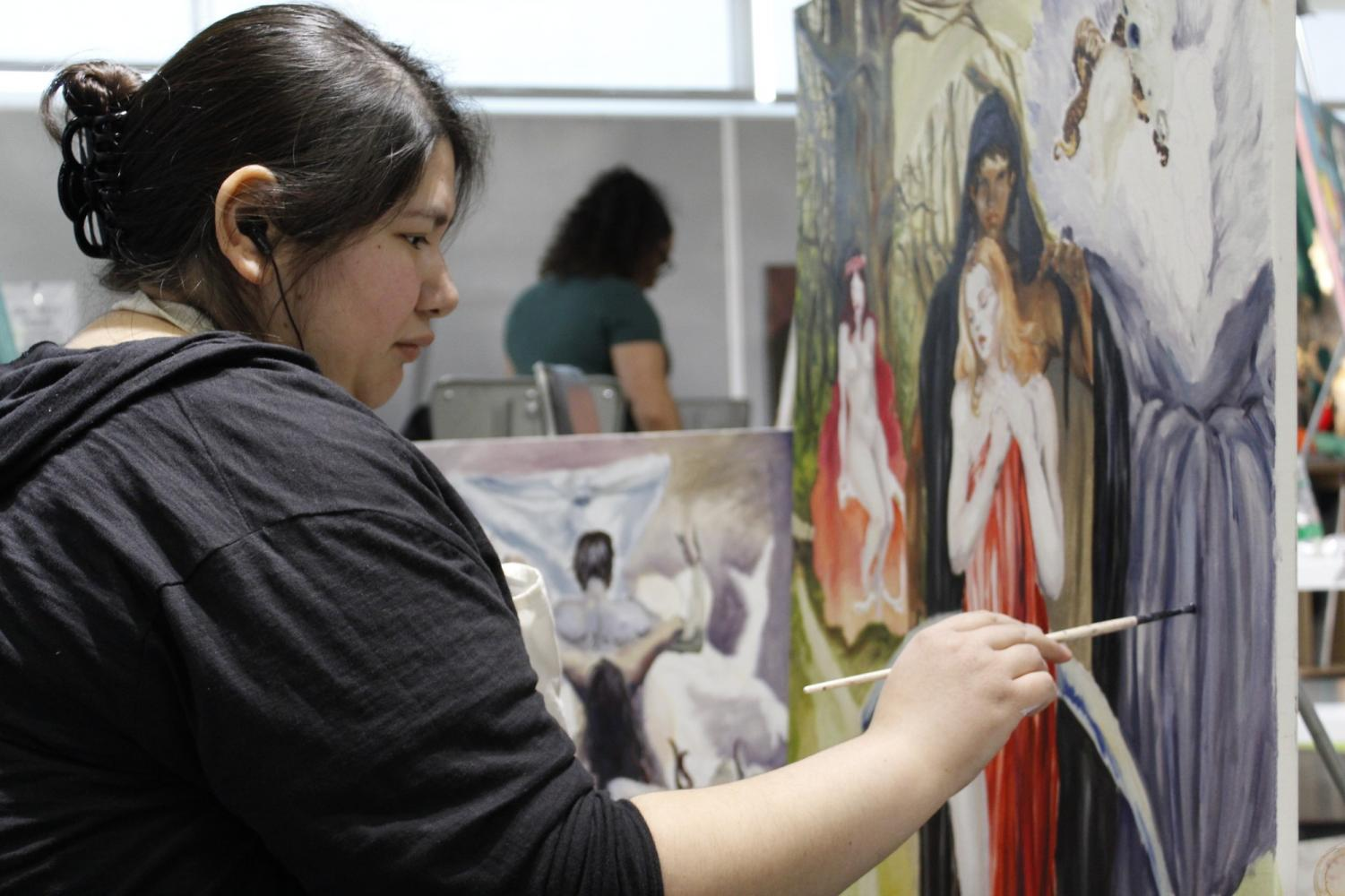Lisa Naranjo, art major, works on a painting that is part of a series of paintings depicting abuse, relationships, over-sexualization and liberation of women.