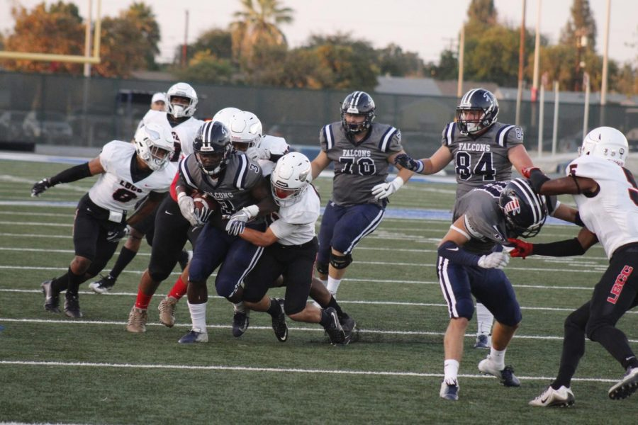 Sophomore running back No. 3 Rhamondre Stevenson carrying the defensive line on his back and pushing through to gain yardage. Stevenson set the Falcons' school record in single-game rushing yards with 339 in the game at Cerritos College against Long Beach City College on Sept. 29, 2018.
