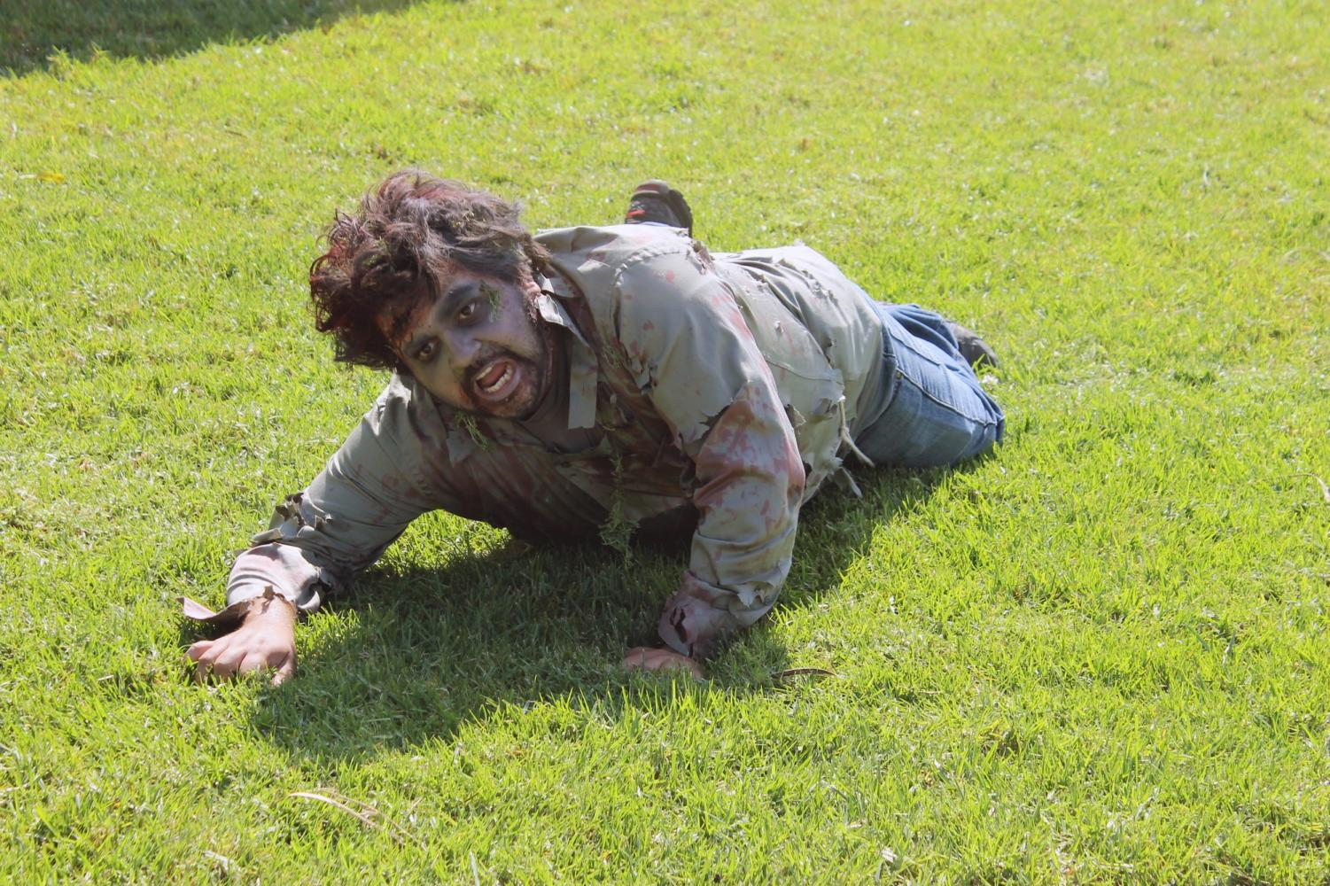Scare actor Armando Avila, crawls towards students who dared to pick up food donations.