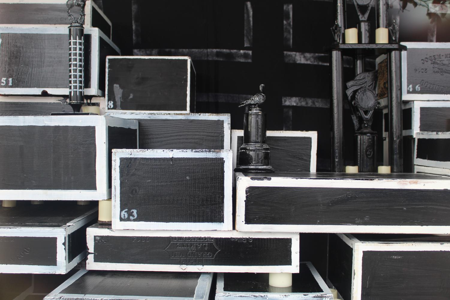 Artist Karim Shuquem crafted a series of boxes each different from one another and stacked in a non specific formation.