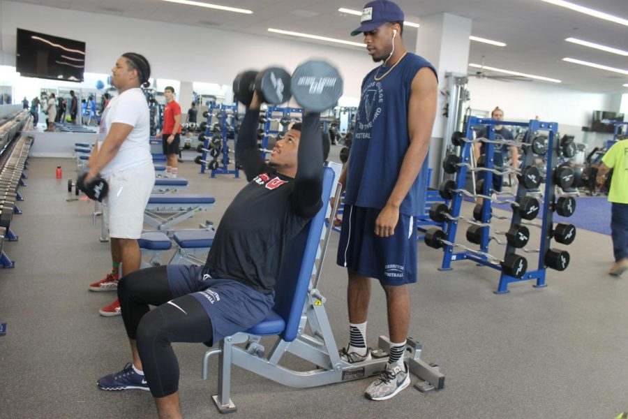 Cerritos+College+running+back+Carl+Odom+gets+a+shoulder+press+lift+in+the+new+weight+room+facility.+